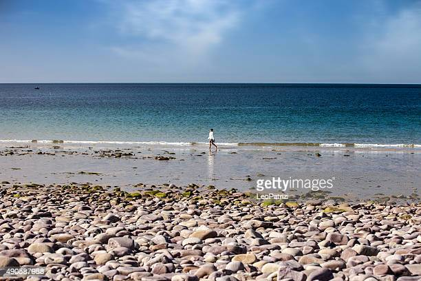 Solitary woman walking on the beach in Brittany