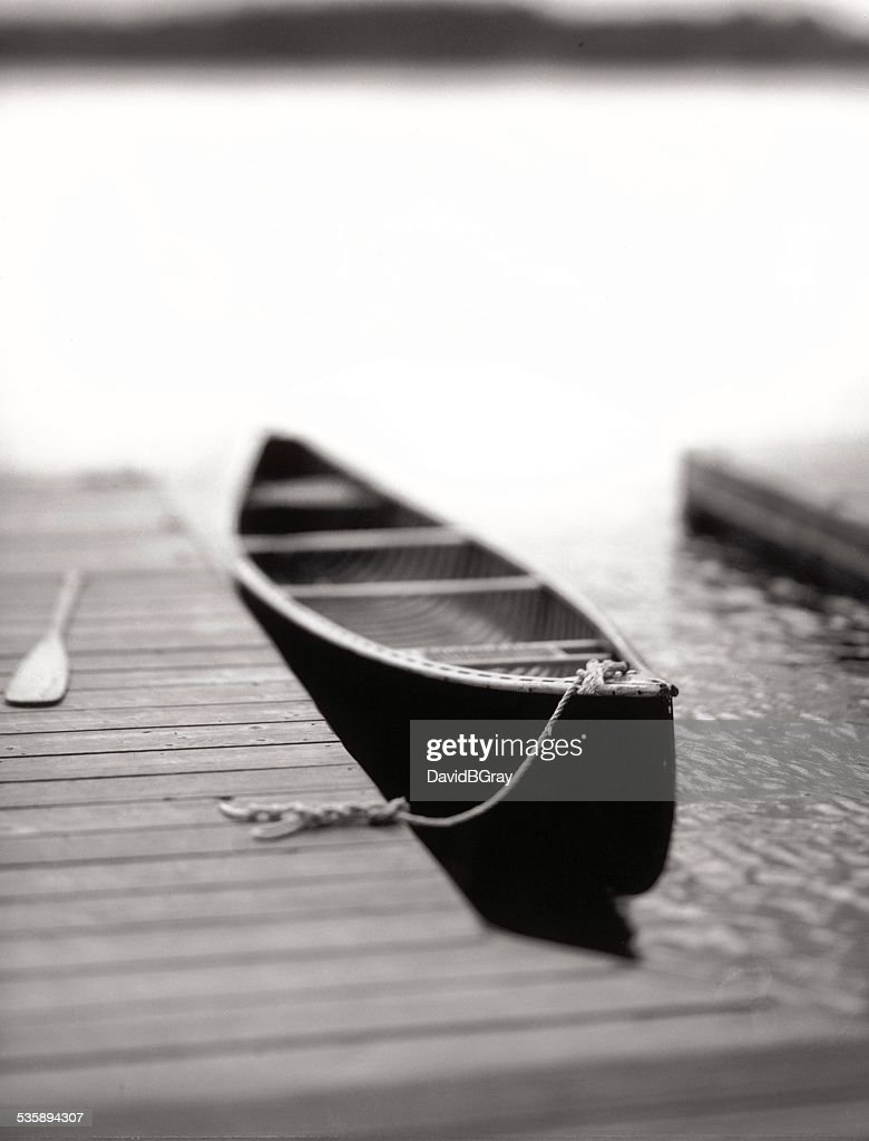 Solitude, tranquility : lone canoe tied to a dock on a lake : Stock Photo