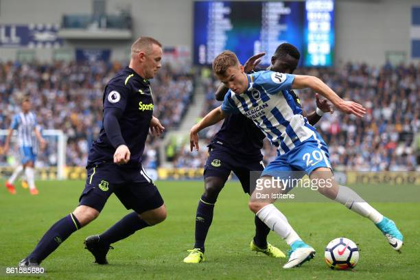 Solly March of Brighton and Hove Albion is tackled by Wayne Rooney of Everton and Idrissa Gueye of Everton during the Premier League match between...