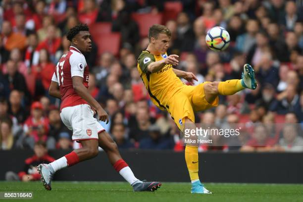 Solly March of Brighton clears under pressure from Alex Iwobi of Arsenal during the Premier League match between Arsenal and Brighton and Hove Albion...