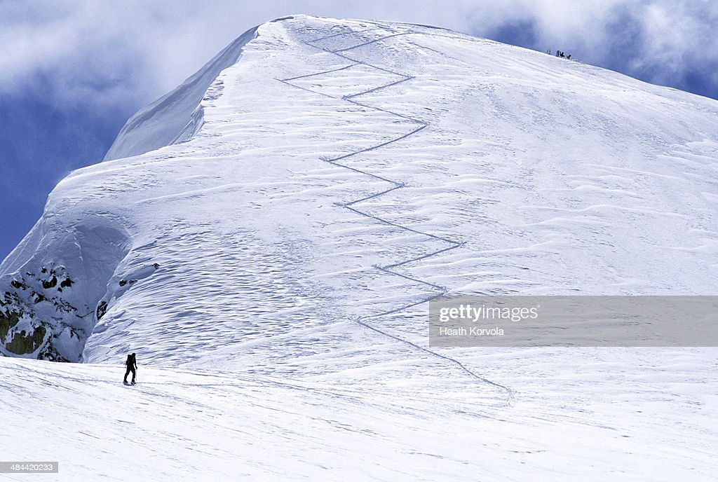 Solo backcountry skier ascending track to peak.