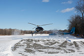 solo black helicopter in blue skies with snow in winter
