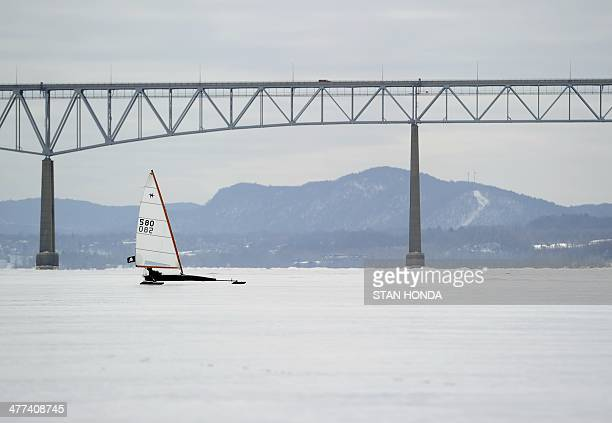 A solo ice boat sails on a frozen Hudson River past the KingstonRhinecliff Bridge March 7 2014 in Barrytown New York These historic 'ice yachts' some...