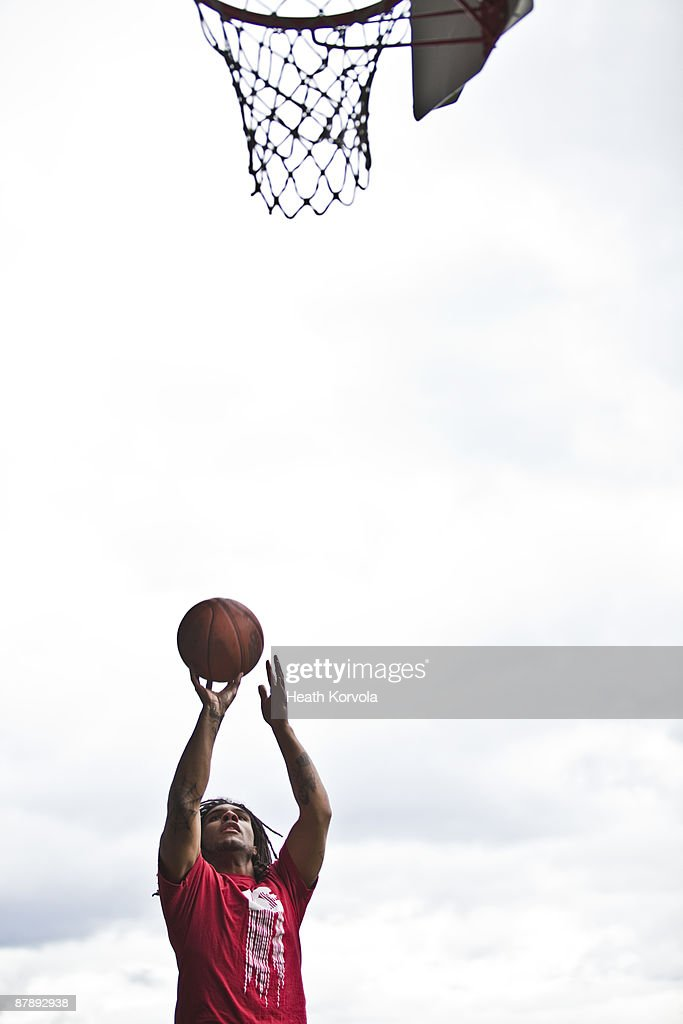 A solo male shooting hoops. : Stock Photo