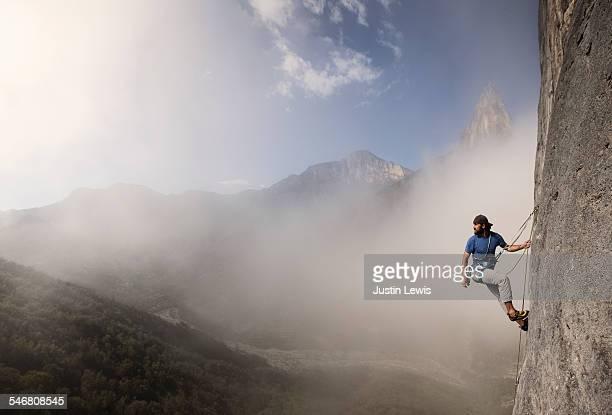 Solo Man Climbs Rock Wall