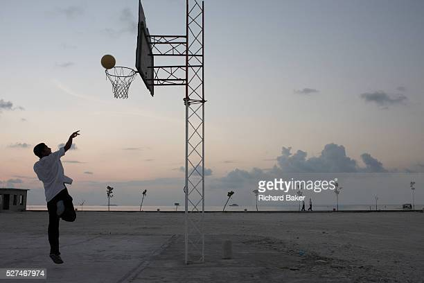 A solo teenage player takes a shot at the net on a basketball court at the Cyprea Marine Foods processing factory on Himmafushi Island Maldives in...