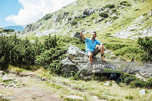 Solo traveler making selfie in the mountain