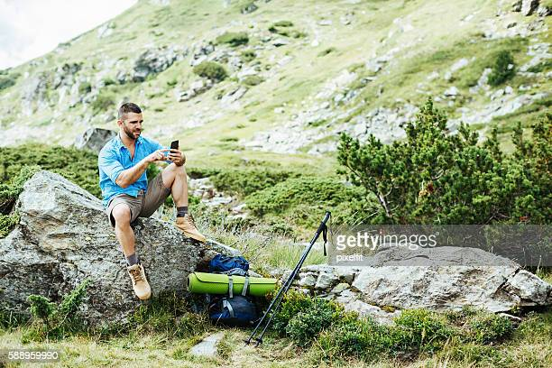 Solo traveler texting on a rock