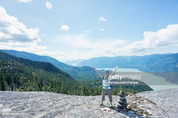 Solo Woman Hiker with Raised Arms Next to Rock Cairn