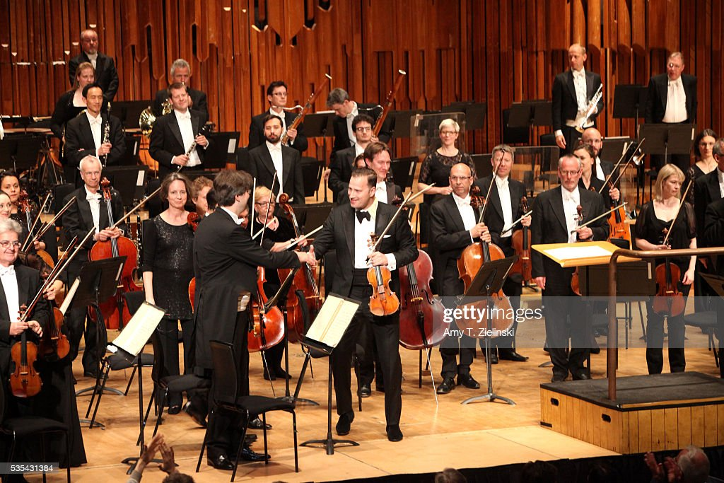 Soloist violinist Nikolaj Znaider shakes hands with the concertmaster before playing the Beethoven Violin Concerto as Sir Antonio Pappano conducts the London Symphony Orchestra at Barbican Centre on May 29, 2016 in London, England.