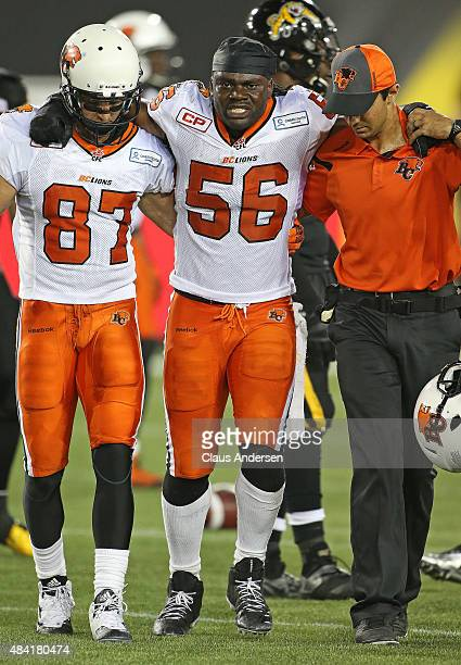 Solomon Elimimian of the BC Lions is helped off the field during play against the Hamilton TigerCats during a CFL football game at Tim Hortons Field...
