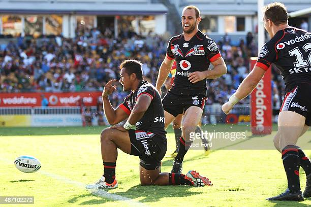 Solomone Kata of the New Zealand Warriors celebrates with teammates Simon Mannering and Ryan Hoffman after scoring a try as he is during the round...