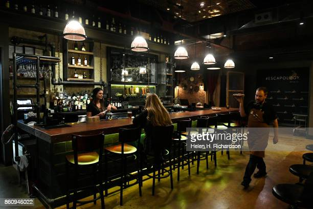 DENVER CO OCTOBER 10 Solutions Lounge bartender and waiter Michael Sievers right carries a tray of food while bartender Rachel Dunning behind bar...