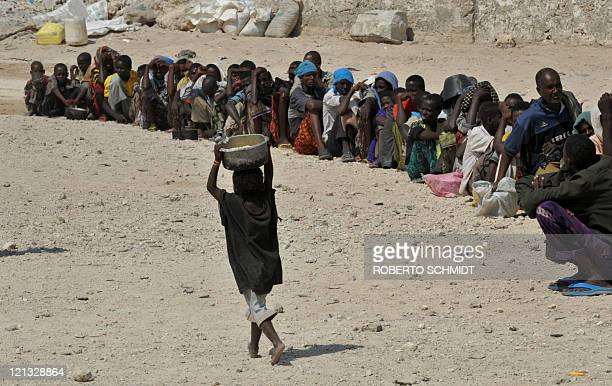 A Somali boy carries a pot filled with a hot meal over his head past others waiting in line at a food distribution point in Somalia's capital...