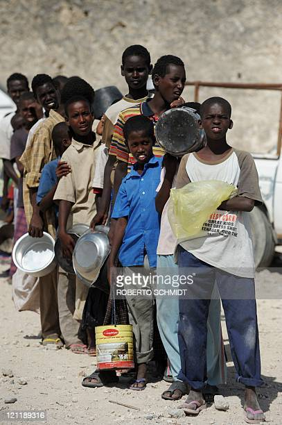 Somali boys living in a camp for Internally Displaced Persons queue in Mogadishu on August 15 to receive cooked meals in the courtyard of a Somali...