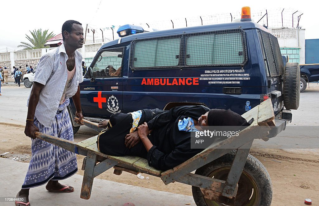 A Somali carries on June 19, 2013 an injured person on a cart after Al-Qaeda linked Shebab insurgents shot and blasted their way into the United Nations (UN) compound in Mogadishu. Three foreigners and at least two Somali security guards were killed during the attack -- the most serious attack on the UN in the troubled country in recent years.