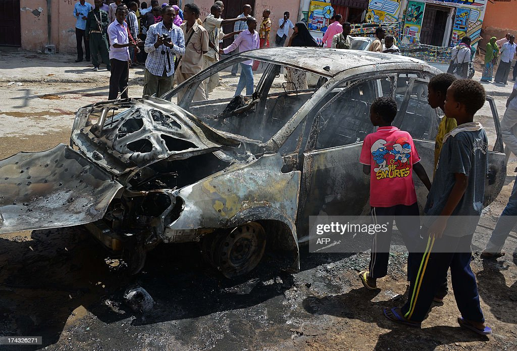Somali children look at a burnt out car after a bomb blast targeted at a Somali MP took place at Hamarweyne Market in Mogadishu on July 24, 2013. At least one civilian died and several were injured in the blast. AFP PHOTO/MOHAMED ABDIWAHAB