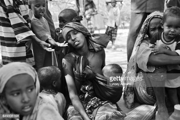 Somali children try to feed a woman biscuits as she suffers from dehydration and hunger moments after arriving at a reception center at the Dadaab...