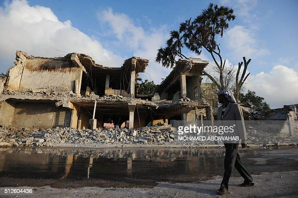 A Somali civilian walks near a destroyed building after the attack on SYL hotel on February 27 2016 in Mogadishu Somalia At least 14 people were...