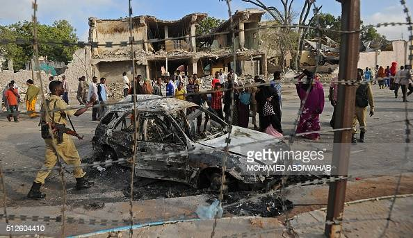 Somali civilians walk past a wreckage car after the attack on SYL hotel on February 27 2016 in Mogadishu Somalia At least 14 people were killed on...