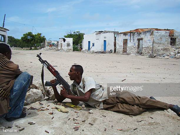 A Somali fighter supporting the Somali Government looks down a street as he holds his weapon during fighting in Mogadishu Somalia on July 12 2009...