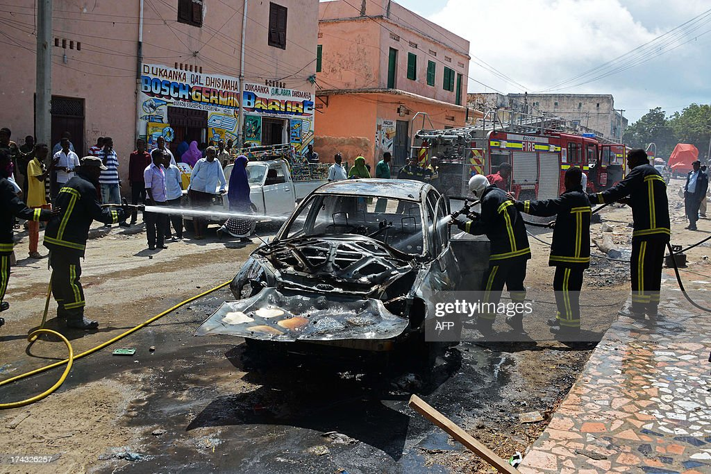 Somali firefighters extinguish a fire in a car after a bomb blast targeted at a Somali MP took place at Hamarweyne Market in Mogadishu on July 24, 2013. At least one civilian died and several were injured in the blast.