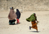 A Somali girl runs towards Somali NGO workers distributing hot meals to Somalis who have been displaced from their homes by the worst drought to hit...