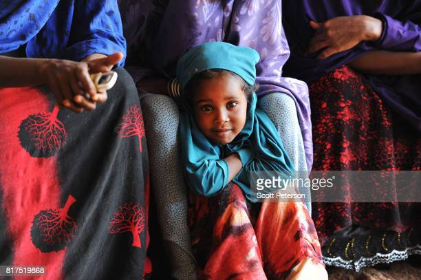 Somali girl watches as villagers who have benefited from food and cash donations mobilized by a WhatsApp group called 'Daryeel' formed by diaspora...