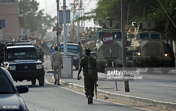 Somali government police officers secure the area of a suicide car bombing near the SYL hotel in Mogadishu on January 22 2015 At least five people...