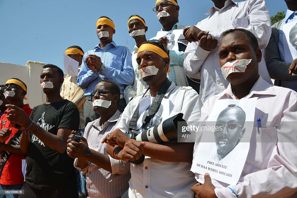 Somali journalists holding up the picture of their colleague arrested, Abdiaziz Abdinor Ibrahim, participate in a meeting for condemning his long term in jail on January, 27, 2013 in Mogadishu. General attorney of Somali nation Abdikadir Mohamed Muse, announced on Saturday that the Somali police investigation on Abdiaziz ended and will be courted. Abdiaziz has been accused of reporting false rape, and giving the women bribery so as to tell lie. Lul Ali Osman, the rape victim told to the journalist she was rapped by five Somali police-dressed men, but the police refused that. AFP PHOTO MOHAMED ABDIWAHAB HAJIABIKAR