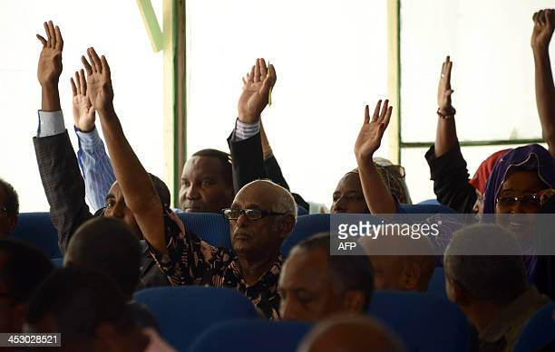 Somali lawmakers raise their hands on December 2 2013 during a parliament session in Mogasishu to impeach Somali Prime Minister Abdi Farah Shirdon...