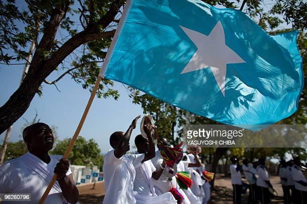 A Somali man holds a Somali flag while others dance during a ceremony feting the first year of President Sharif Sheikh Ahmed's shaky rule at Villa...