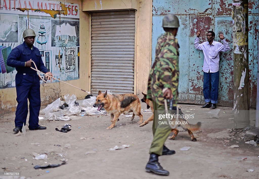 A Somali man is cornered by Kenyan police with guard dogs in the somali district of Eastleigh in Nairobi on November 19, 2012. Police used tear gas and fired into the air to contain the violence which erupted after a bomb exploded in Eastleigh on November 18 2012 killing seven people and wounding many more. Kenyan residents in Eastleigh turned on Somalis and attacked their shops and stalls, accusing them of being responsible for the bomb. AFP PHOTO/CARL DE SOUZA