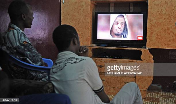 Somali men watch on September 6 2014 in Mogadishu news on a television channel broadcasting a portrait of Somalia's AlQaedalinked Shebab slain leader...
