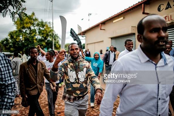 TOPSHOT Somali migrants armed with a machete and rocks dmonstrate in the Marabastad neighbourhood in Pretoria on February 24 2017 South African...