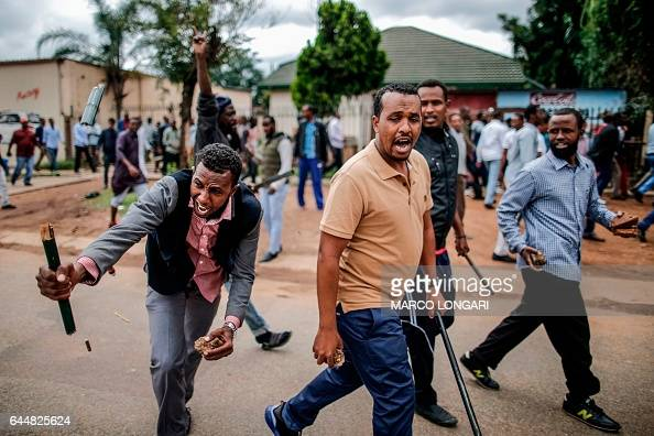 TOPSHOT Somali migrants armed with rocks and sticks march in the Marabastad neighbourhood in Pretoria on February 24 2017 South African police fired...