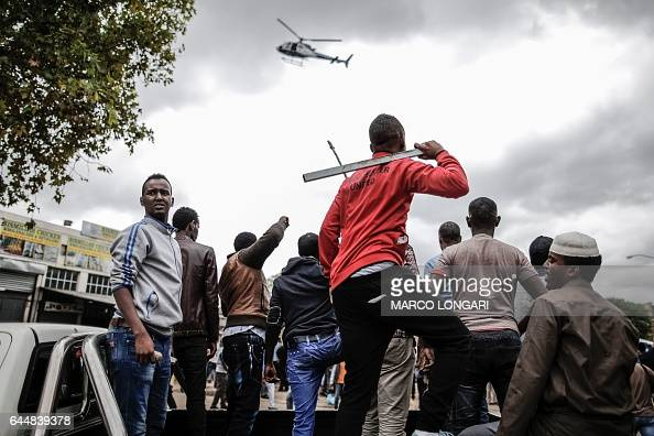 TOPSHOT Somali migrants armed with rocks and sticks watch from the back of a pick up truck as a police helicopter hover over an antiimmigration march...