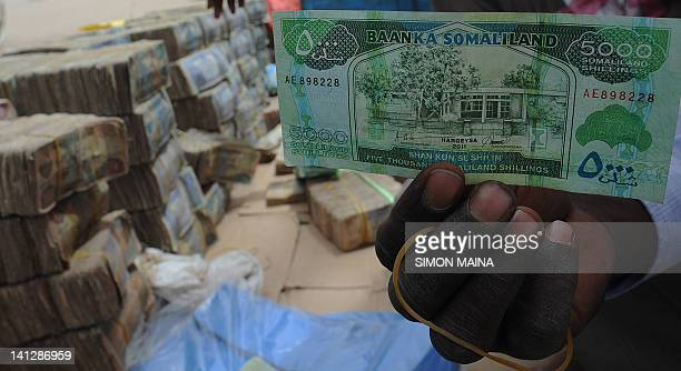 Somali money changer holds a banknote on March 8 2012 next to piles of money on the dusty street of Hargeisa in Somaliland the northern breakaway...
