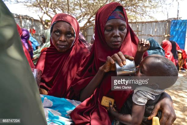 Somali mother gives water to her child at a World Food Program humanitarian aid registration center in Mogadishu According to an United Nations...
