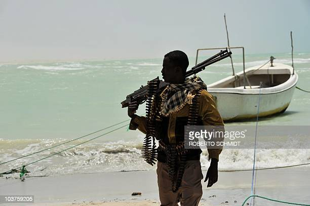 Somali part armed militia part pirate carries his highcaliber weapon on a beach in the central Somali town of Hobyo on August 20 2010 Hobyo has no...