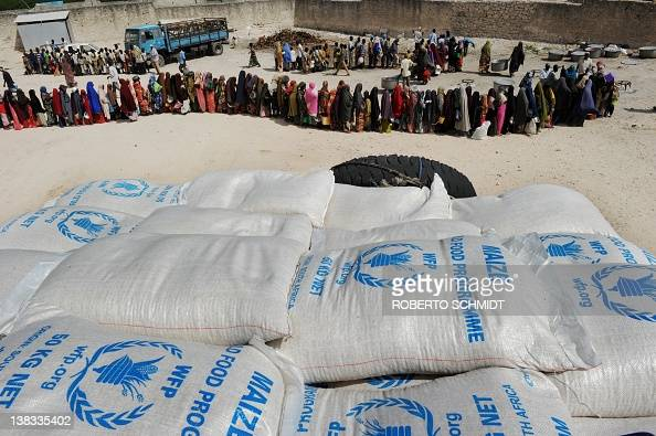 Somali people living in nearby camps for Internally Displaced Persons queue in Mogadishu on August 15 to receive cooked meals in the courtyard of a...