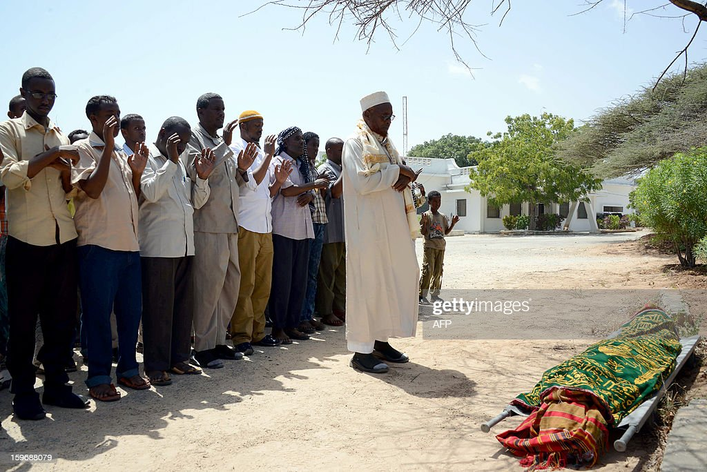 Somali people stands on January 18, 2013 in Mogadishu, in front of the body of Somali journalist Abdihared Osman Adan, who was shot dead today by Unidentified gunmen. Abdihared Osman Adan, a presenter at the private Radio Shabelle was shot several times near his house in Mogadishu's Wadajir district. AFP PHOTO / Mohamed Abdiwahab