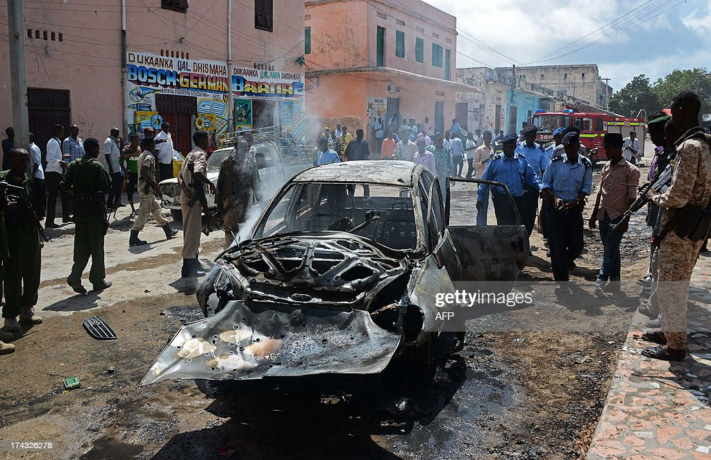 Somali police and security forces look at a burnt out car after a bomb blast targeted at a Somali MP took place at Hamarweyne Market in Mogadishu on July 24, 2013. At least one civilian died and several were injured in the blast.