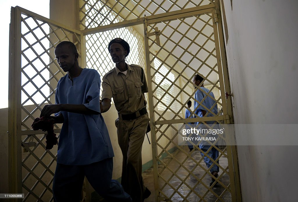 A Somali prison warden ushers an inmate through gates at a prison block at the UNfunded prison in Hargeisa the capital of Somalia's selfdeclared...