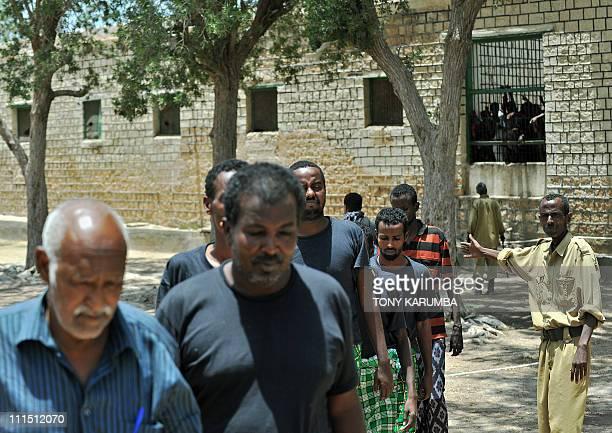 A Somali prison warder leads Somali men convicted of piracy back to their cells at Berbera prison in Somalia's breakaway Republic of Somaliland on...