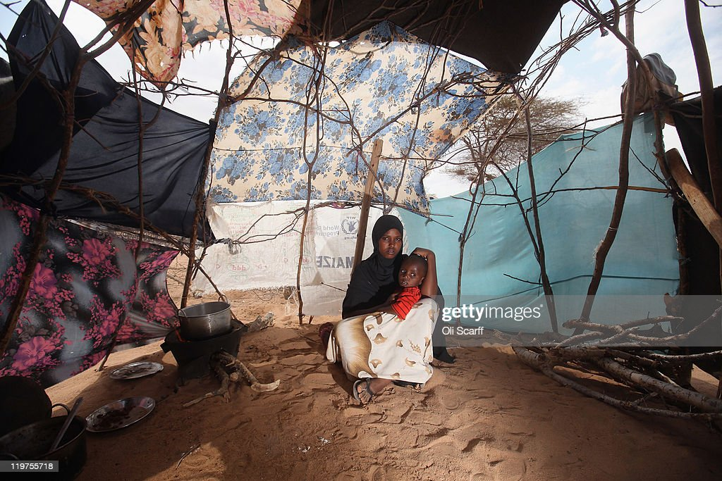 Somali refugee mother and child sit in their makeshift hut on the edge of the Hagadera refugee camp which makes up part of the giant Dadaab refugee...