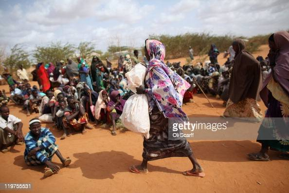 Somali refugee woman holding a bag of food aid walks past those waiting at the entrance to the registration area of the IFO refugee camp which makes...