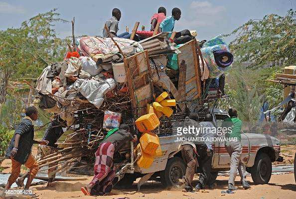 Somali refugees carry their belongings after their temporary shelters were destroyed by Somali soldiers on March 4 2015 at the Sarkusta refugee camp...