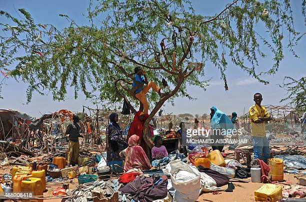 Somali refugees stand amongst their scattered belongings after their temporary shelters were destroyed by Somali soldiers on March 4 2015 at the...