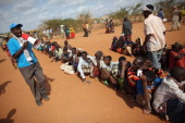 Somali refugees wait at the entrance to the registration area of the IFO refugee camp which makes up part of the giant Dadaab refugee settlement on...